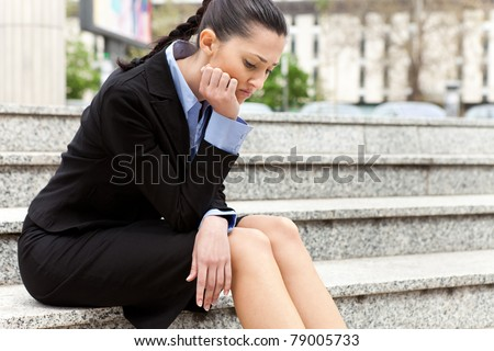 businesswoman sitting on the stairs of the company troubled after getting the news he was fired - stock photo