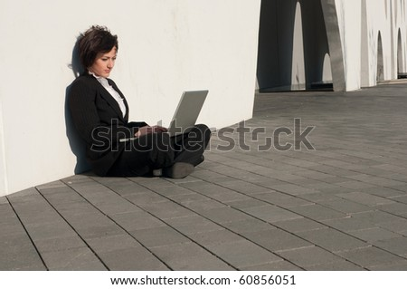 Businesswoman sitting with a laptop at the wall outdoors - stock photo