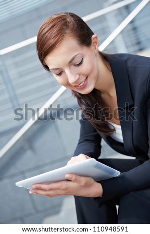 Businesswoman sitting with Digital Tablet Computer on stairs - stock photo