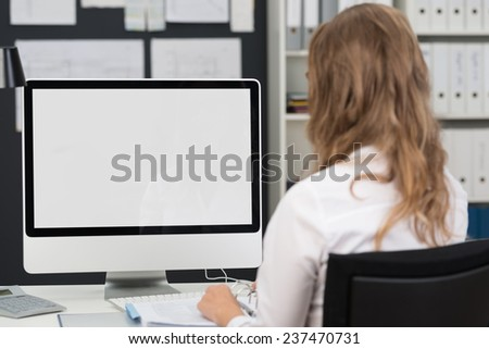 Businesswoman sitting with her back to the camera working at a desktop computer with the blank screen visible to the viewer - stock photo
