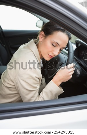 Businesswoman sleeping on the wheel in her car - stock photo