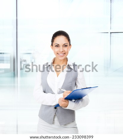 Businesswoman smile, hold blue folder clipboard paper document, young attractive business woman in modern office