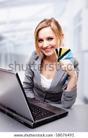 Businesswoman smiling and holding credit cards - stock photo