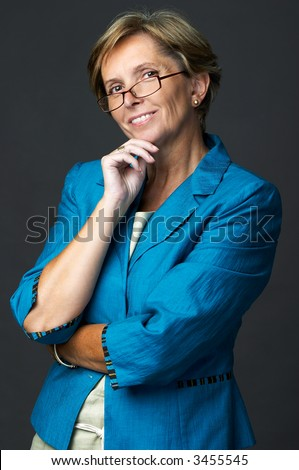 Businesswoman smiling and looking at camera, studio-shot - stock photo