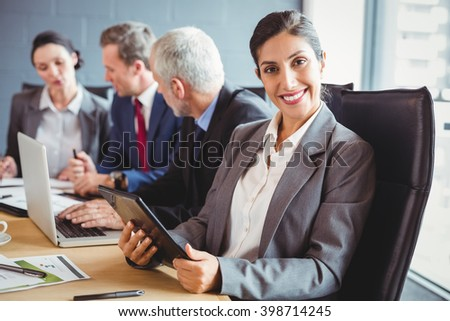 Businesswoman smiling at camera and businesspeople interacting in background in conference room during meeting - stock photo