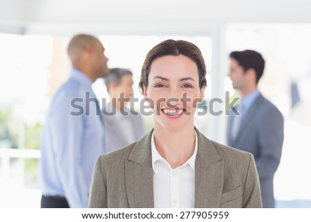 Businesswoman smiling at camera while her colleagues discussing in the office - stock photo