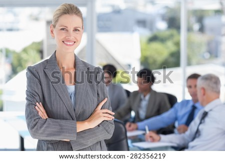 Businesswoman smiling at camera with colleagues behind in the office - stock photo