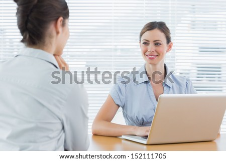 Businesswoman smiling at interview candidate at desk in office - stock photo