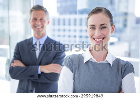 Businesswoman smiling at the camera while her colleague smiling in the background - stock photo