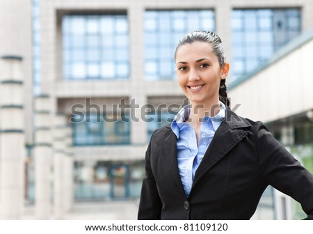 businesswoman smiling at the camera while standing in front of an office building, horizontal shot - stock photo