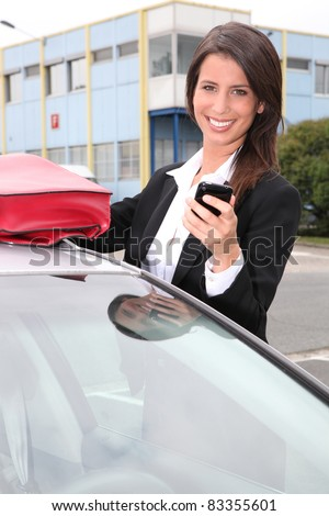 Businesswoman smiling on the phone next to her car - stock photo