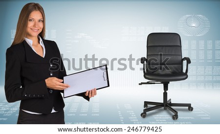Businesswoman smiling showing blank clipboard. Hi-tech graphs with various data as backdrop