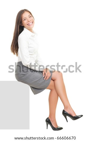 Businesswoman smiling sitting on blank empty billboard sign. Beautiful happy mixed race Asian / Caucasian female model isolated on white background. - stock photo
