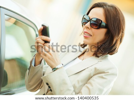 Businesswoman,smiling, using a smart phone. - stock photo