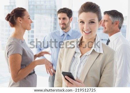 Businesswoman smiling while at work with co-workers while on phone - stock photo