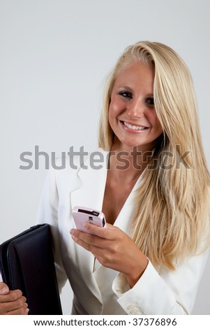 Businesswoman smiling with a cell phone and laptop