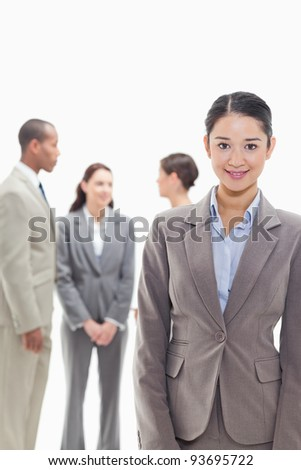Businesswoman smiling with co-workers talking in the background against white background