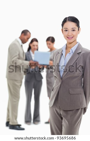 Businesswoman smiling with co-workers watching a laptop in the background against white background - stock photo