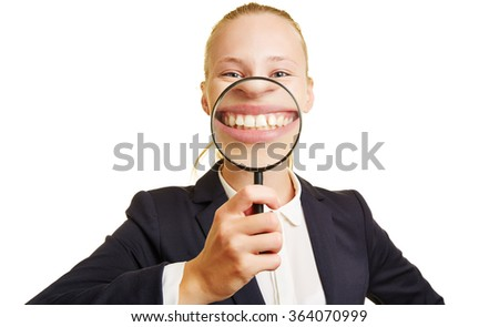 Businesswoman smiling with her mough behind a magnifying glass - stock photo