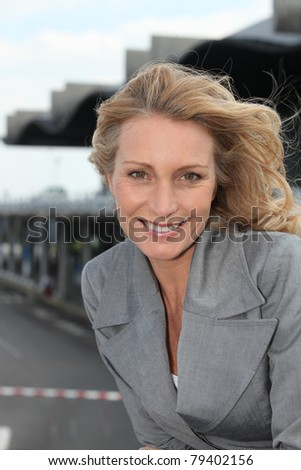 Businesswoman smiling with wind in hair - stock photo