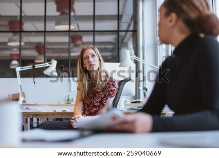 Businesswoman speaking with her colleague in office. Young woman sitting at her desk discussing work with coworker. - stock photo