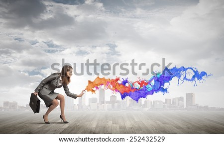 Businesswoman spraying colorful paint splashes from container - stock photo