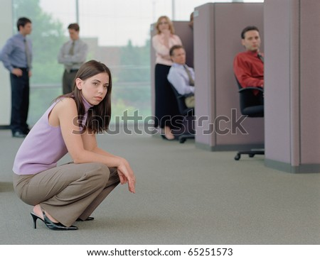Businesswoman squatting on the floor of office