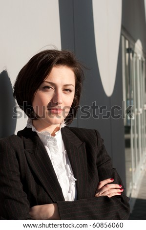 Businesswoman standing and posing at the wall outside - stock photo
