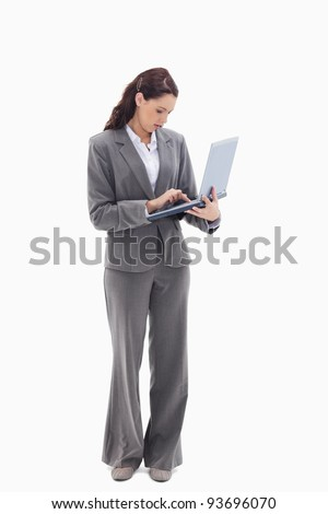 Businesswoman standing and typing on a laptop against white background - stock photo