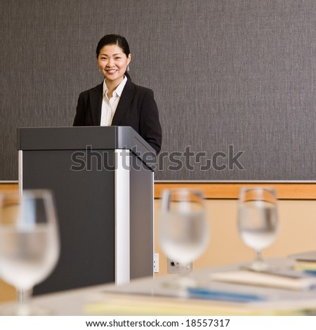 Businesswoman standing behind podium preparing to give presentation in conference room - stock photo