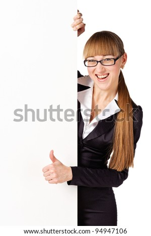 Businesswoman standing beside a billboard and showing thumb up. Isolated over white - stock photo
