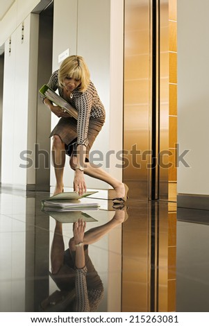 Businesswoman standing beside office elevator, picking up folder from floor, surface level