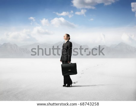Businesswoman standing in a desert