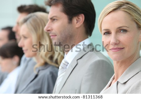 Businesswoman standing in a line with colleagues - stock photo