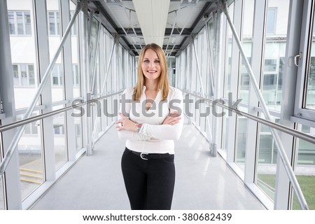 Businesswoman standing in a modern Building with a white shirt and black pants - stock photo