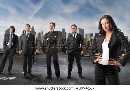 businesswoman standing in front of businessmen team - stock photo