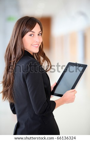 Businesswoman standing in hall with electronic pad