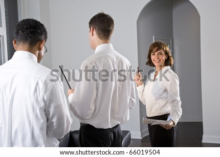 Businesswoman standing in meeting with colleagues reading report