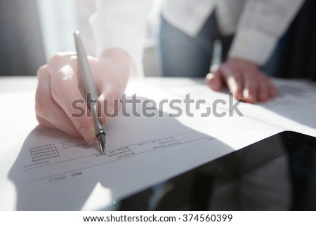 Businesswoman standing in office, writing in planner