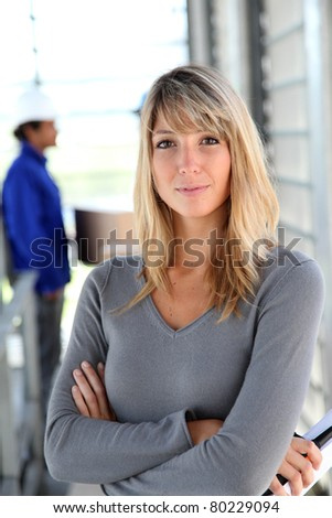 Businesswoman standing in warehouse - stock photo