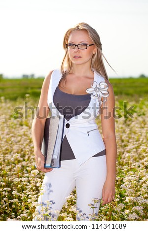 businesswoman standing on a field holding big folder - stock photo