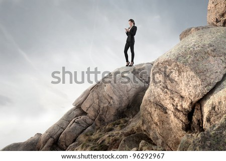 Businesswoman standing on a peak in the mountains and using a mobile phone - stock photo