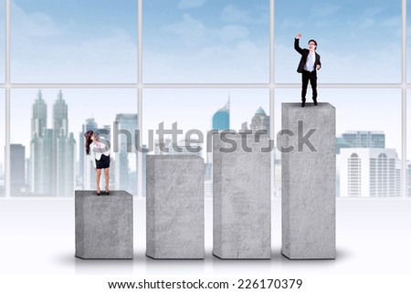 Businesswoman standing on chart lower than her rival, symbolizing business competition - stock photo