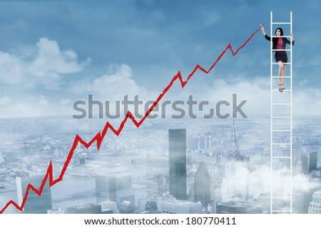 Businesswoman standing on ladder and drawing graph - stock photo