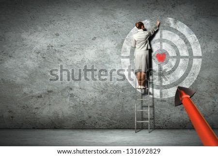 Businesswoman standing on ladder and pointing at target on wall - stock photo