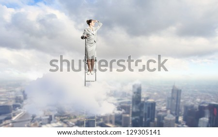 Businesswoman standing on ladder looking into distance against city background