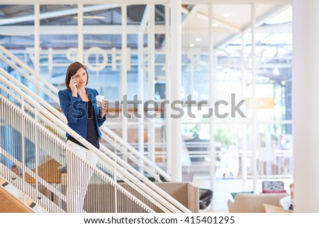 Businesswoman standing on stairs in bright office space with pho - stock photo