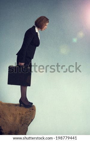 businesswoman standing on the edge of a cliff - stock photo