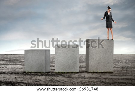 Businesswoman standing on the edge of a cube