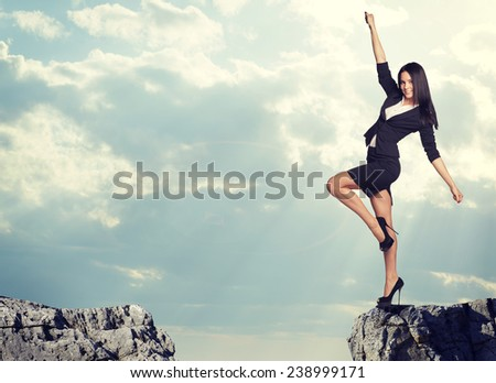 Businesswoman standing on the edge of rock gap in cheerful pose as if going to leap across it. Sky and clouds as backdrop - stock photo